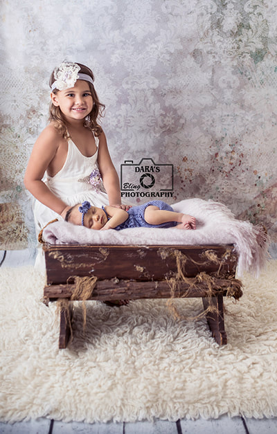 Hollywood Beach newborn photographer big sister with newborn baby sister in cradle